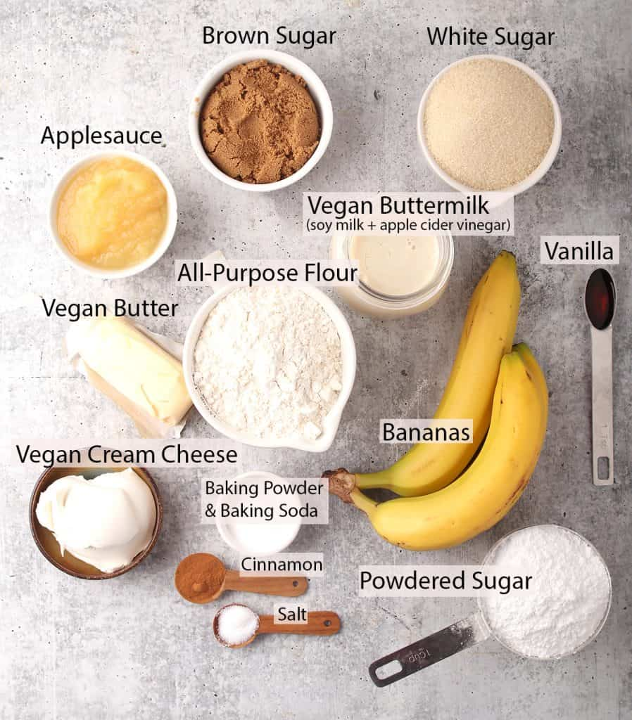 ingredients for making vegan banana cake recipe with cream cheese frosting laid out on a grey table