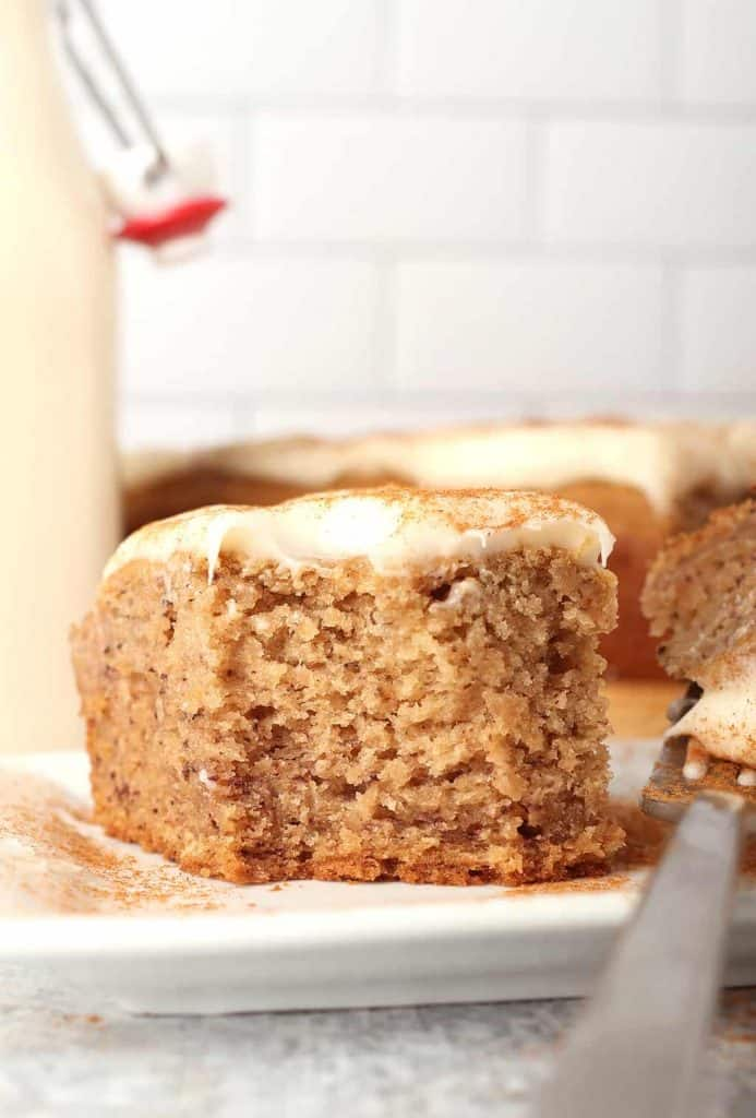 slice of vegan banana cake with cream cheese frosting that has been dusted with cinnamon