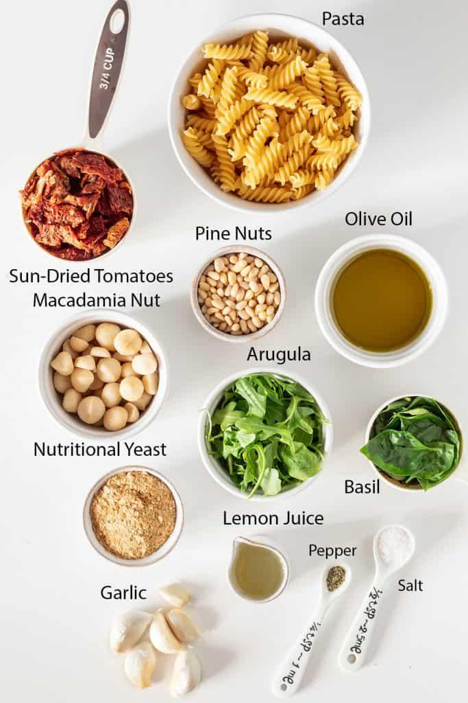 ingredients for vegan pesto pasta recipe measured out into white bowls
