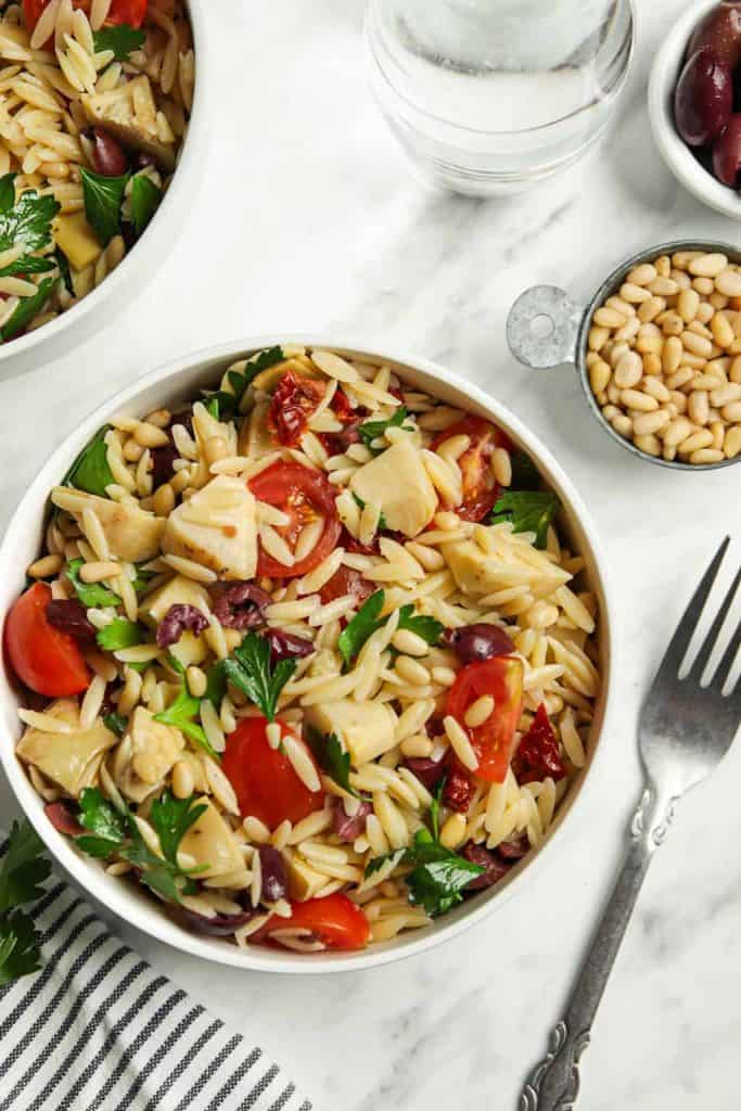 Mediterranean Orzo Salad in a white bowl with a fork next to it.