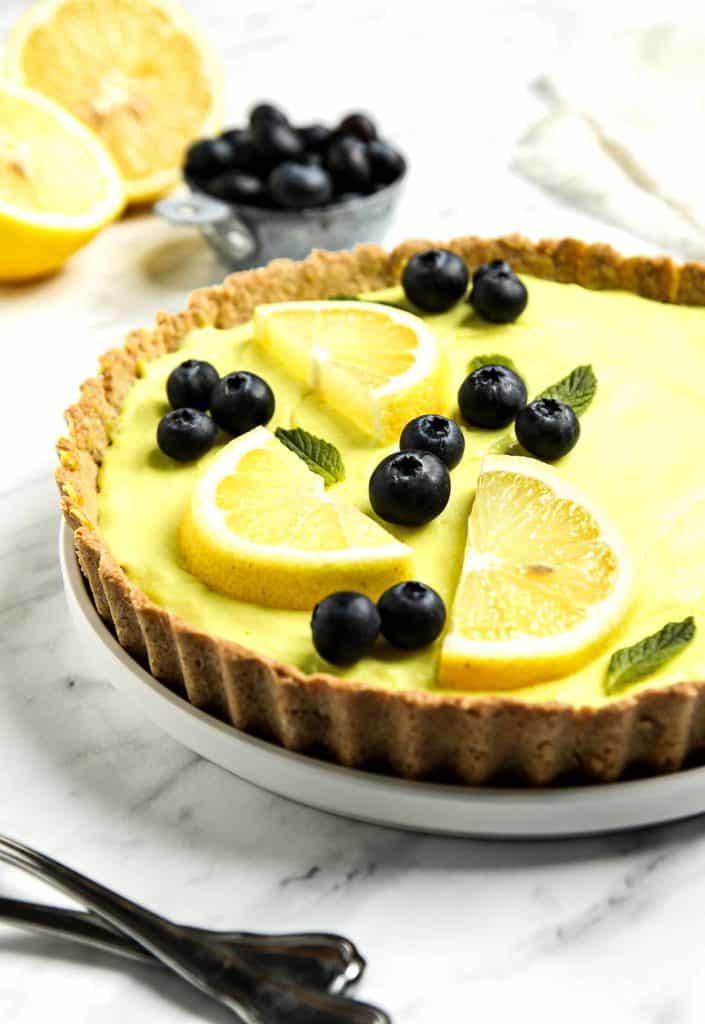 vegan lemon tart topped with lemon slices and blueberries