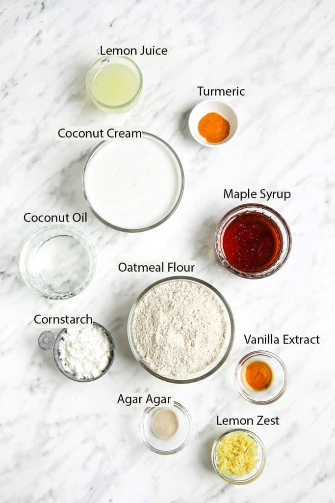 Vegan lemon tart ingredients: lemon juice, turmeric, coconut cream, maple syrup, coconut oil, oatmeal flour, cornstarch, agar agar, vanilla extract and lemon zest