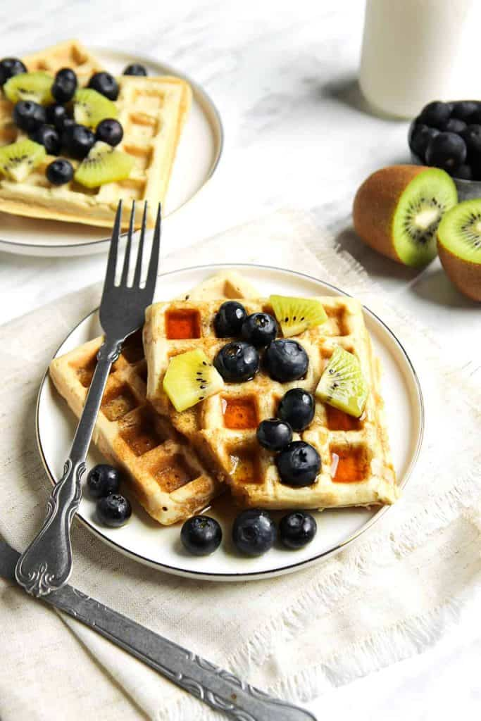 classic vegan waffles served on a white plate with a fork, blueberries, kiwi and maple syrup.