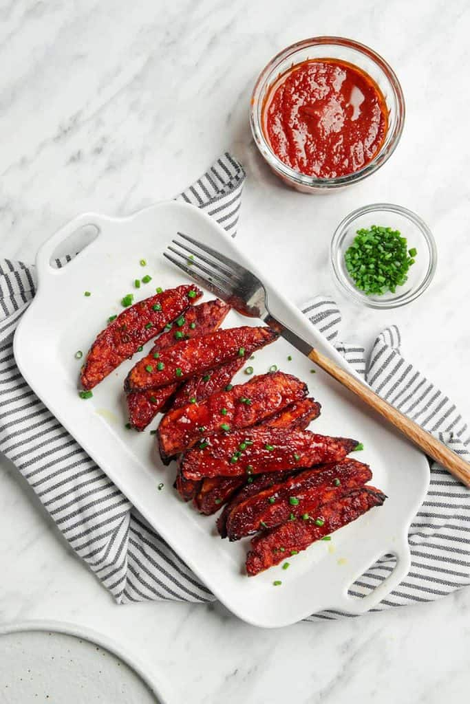Vegan ribs made with tempeh served on a white plate with a fork and green onions