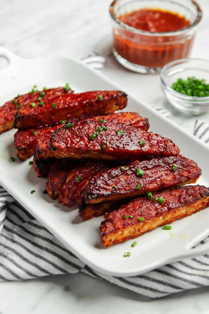 vegan BBQ tempeh served on a white plate garnished with chives