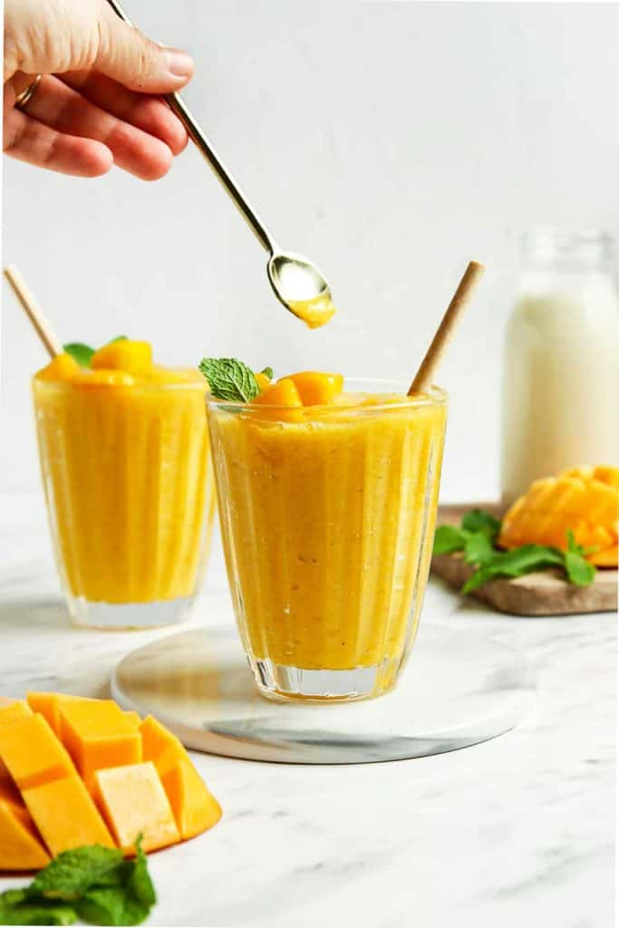 Finished mango smoothies in two glasses with fresh mango and mint.