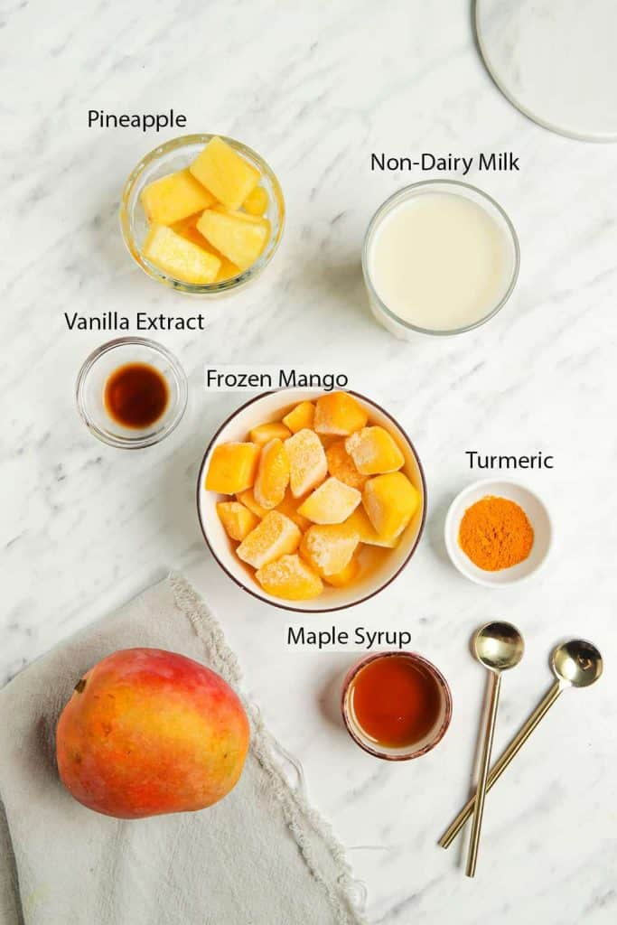 Ingredients for mango smoothie measured out and placed into small bowls on a marble countertop