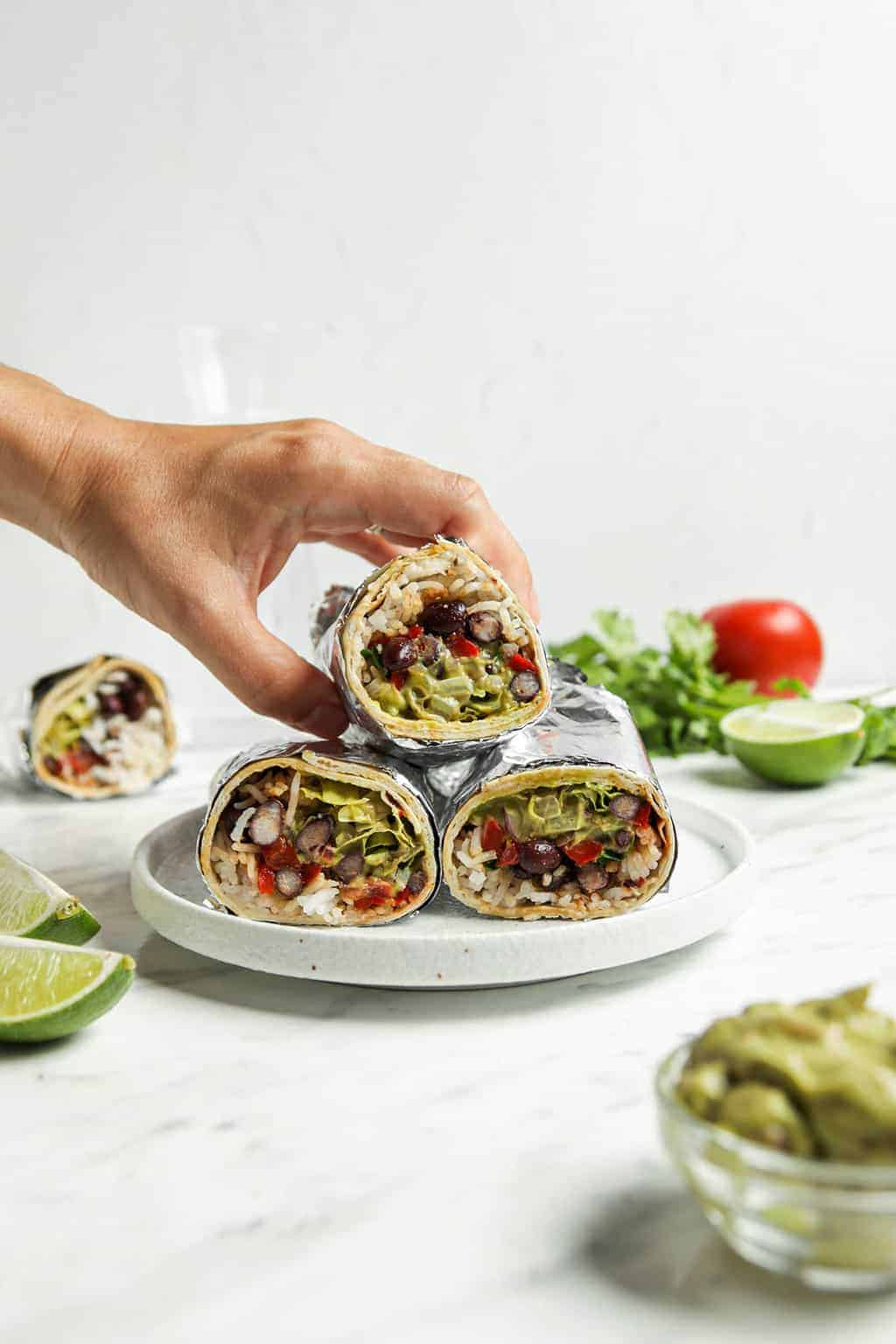 front view of hand picking up a burrito from a stack of three.