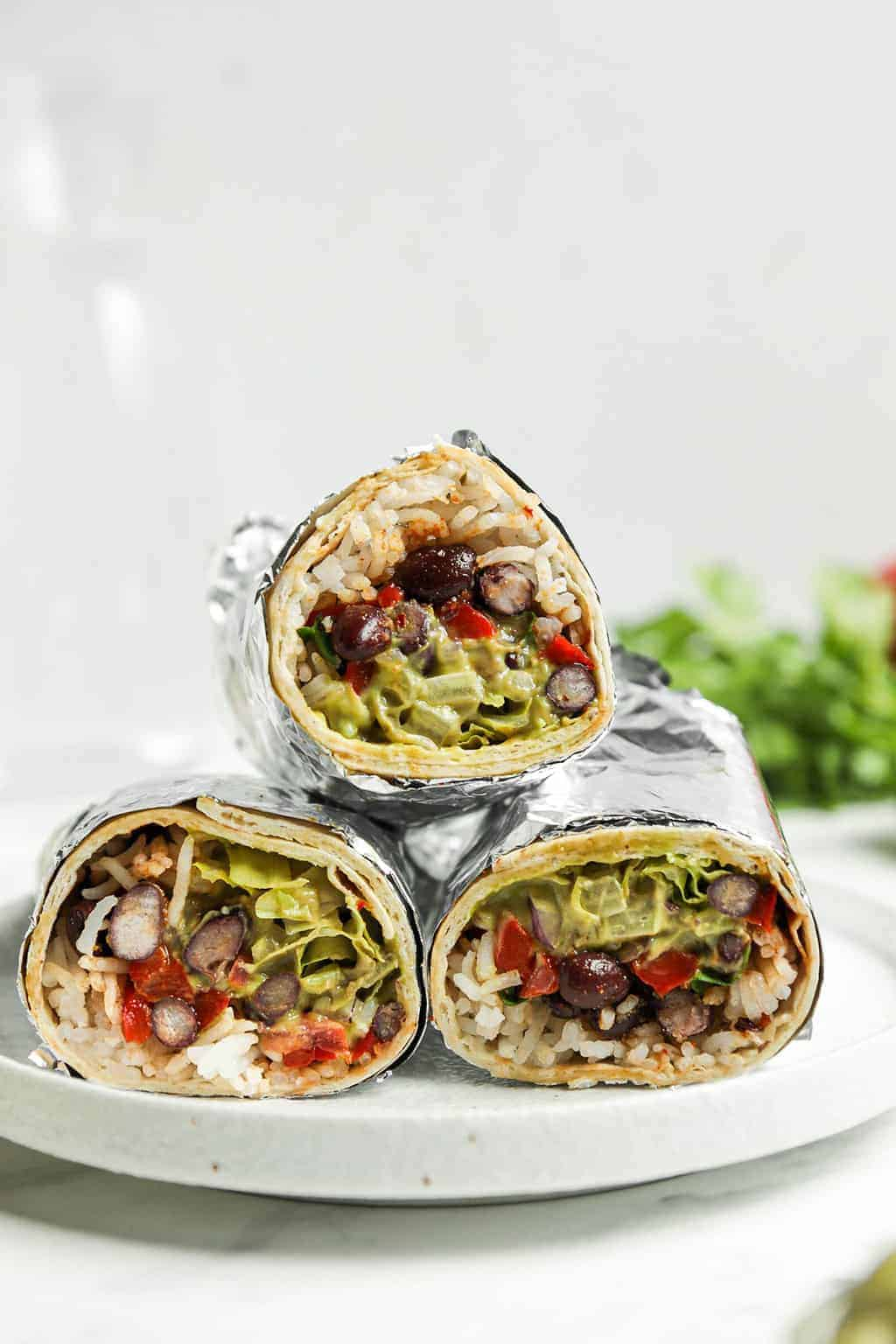 Three vegan burritos wrapped in foil and stacked on a white plate