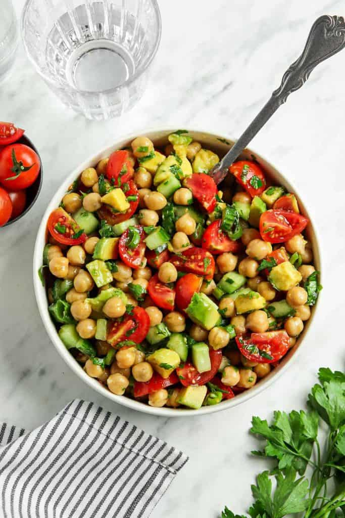 top view of Mediterranean chickpea salad in white bowl with spoon