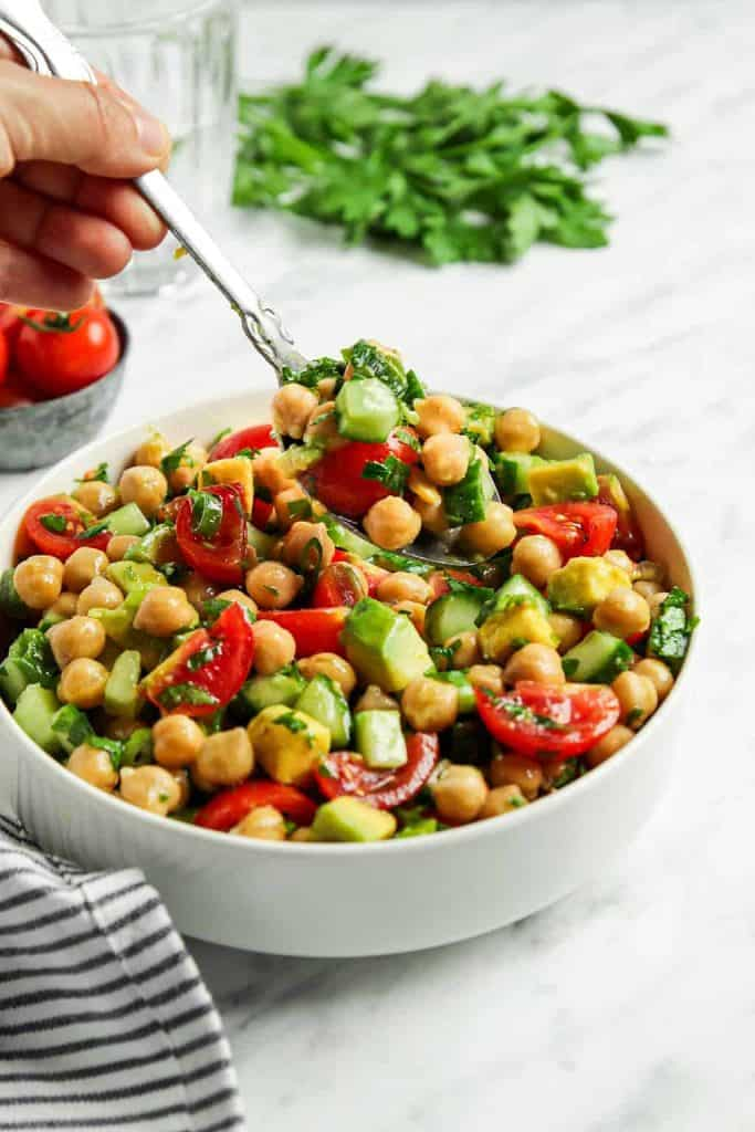 front view of Greek chickpea salad in white bowl with spoon