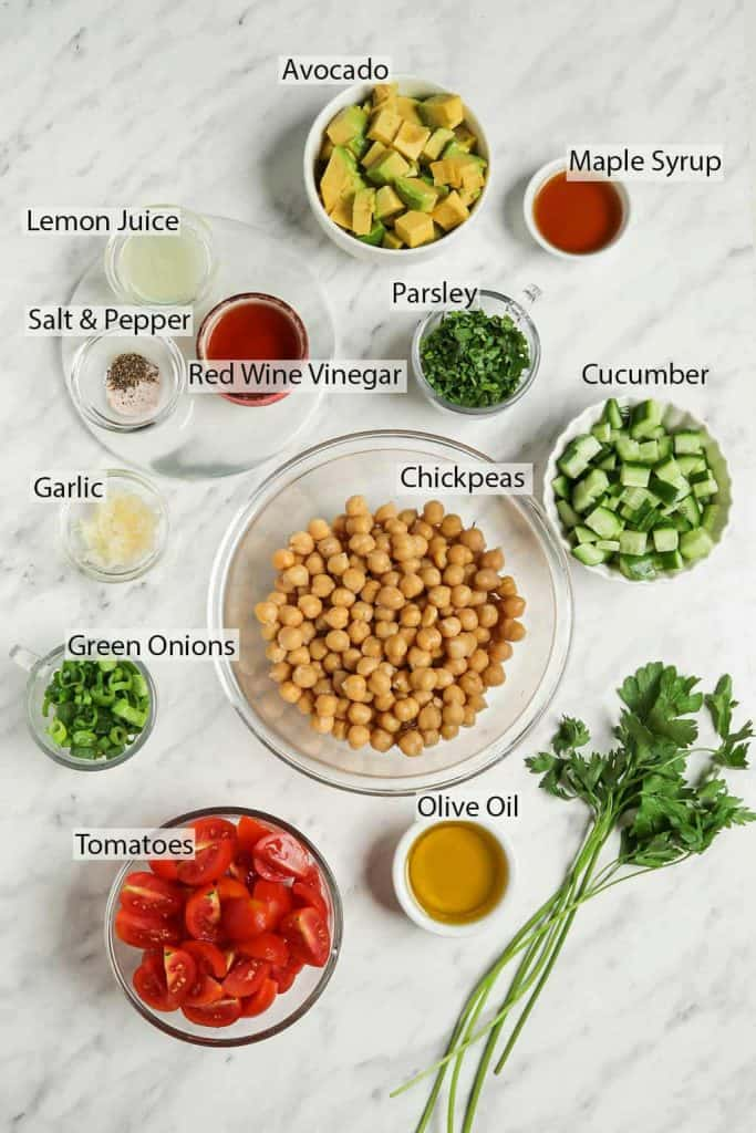 top view of olive oil, parsley, cucumbers, chickpeas, parsley, maple syrup, avocado, red wine vinegar, lemon juice, salt and pepper, garlic, green onions, and tomatoes