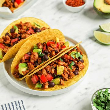 three tacos on white plate