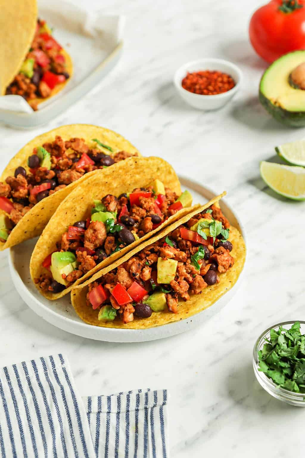 three vegan tacos on white plate with lime slices