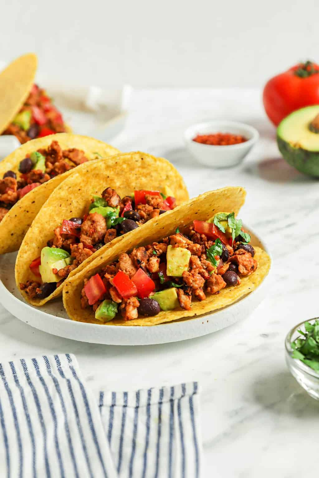 close up of three classic vegan tacos on white plate