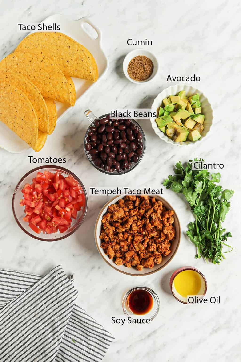 ingredients for homemade tacos including tempeh, cilantro, oil, soy sauce, tomatoes, avocado, black beans, cumin, and taco shells