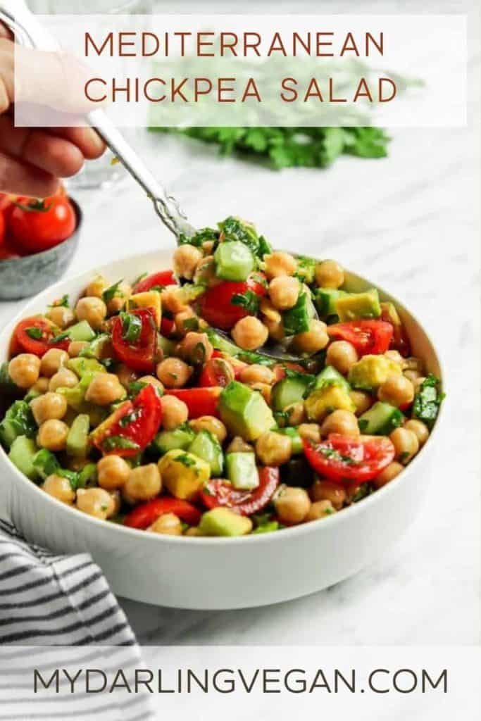 Greek chickpea salad in white bowl with spoon