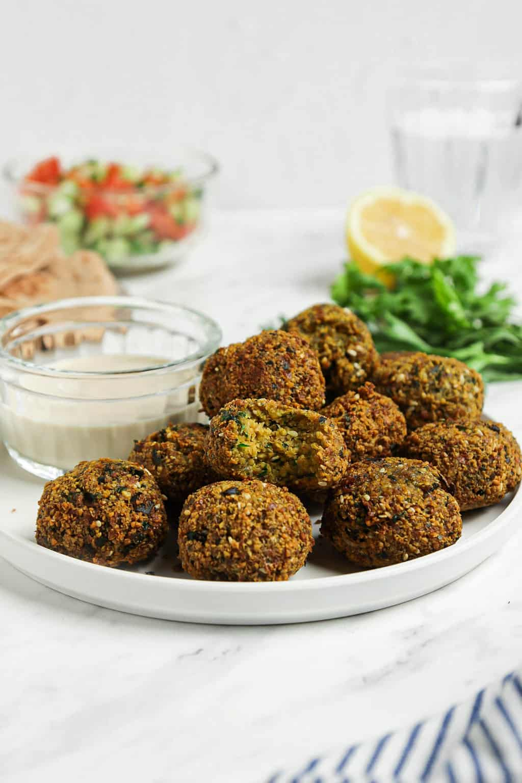 front view of authentic falafel on white plate with sauce