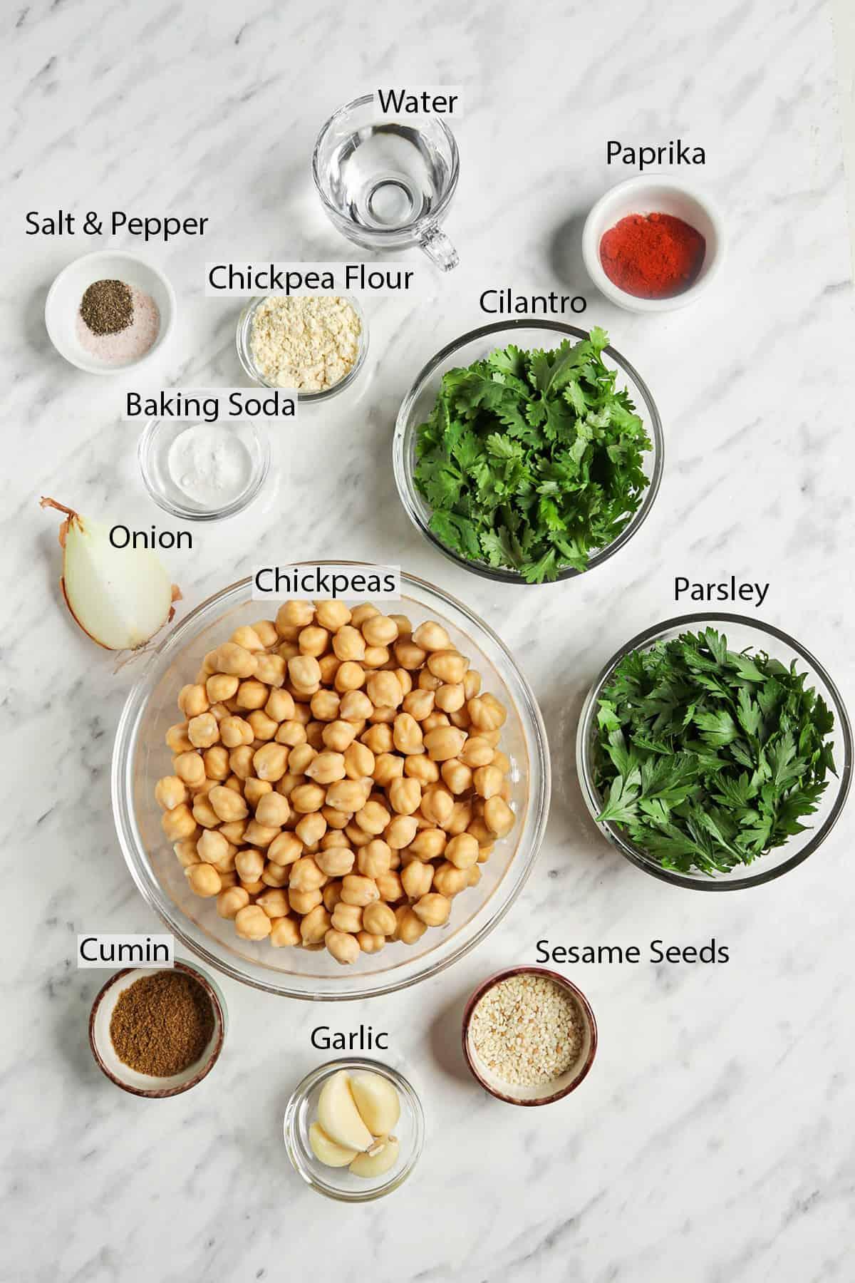 chickpeas, parsley, cilantro, sesame seeds, garlic, cumin, onion, baking soda, salt, pepper, water, chickpea flour, paprika