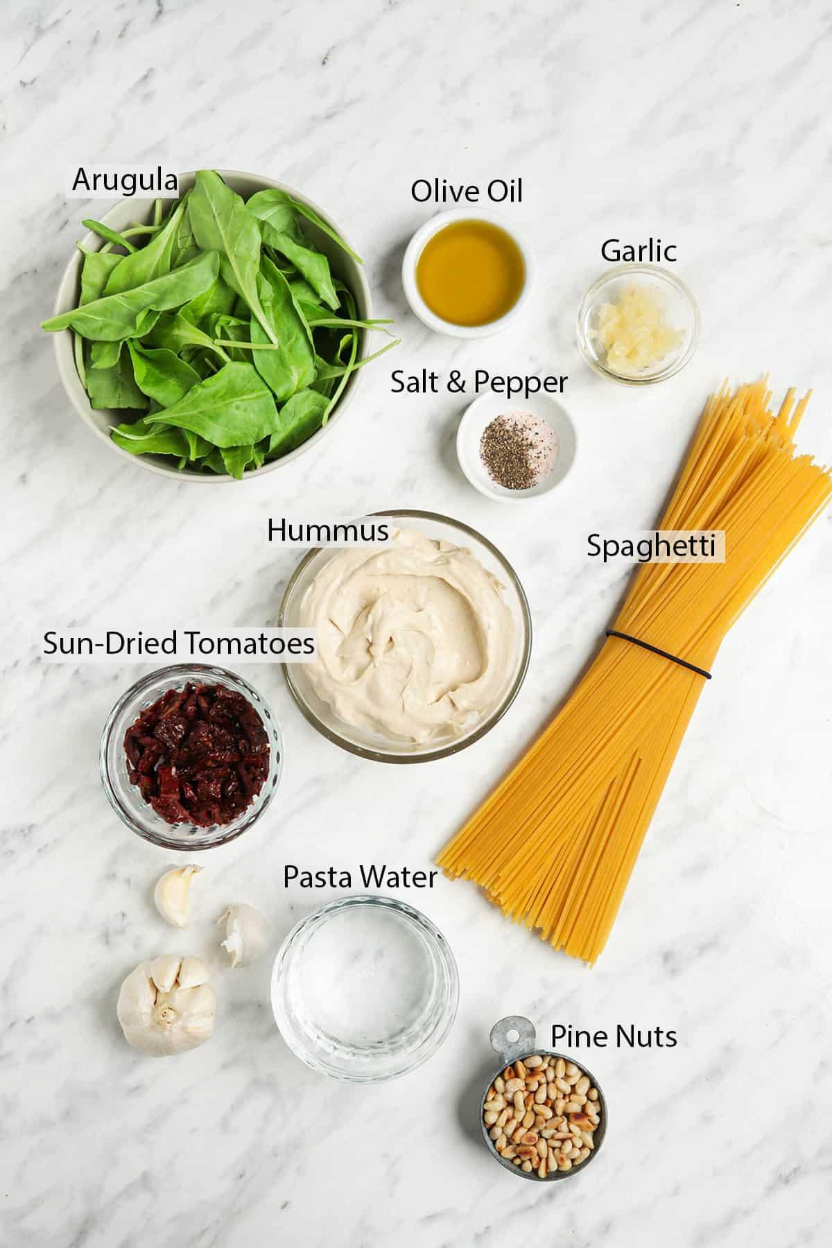 hummus, arugula, salt, pepper, spaghetti, sun-dried tomatoes, pasta water, garlic, olive oil, pine nuts