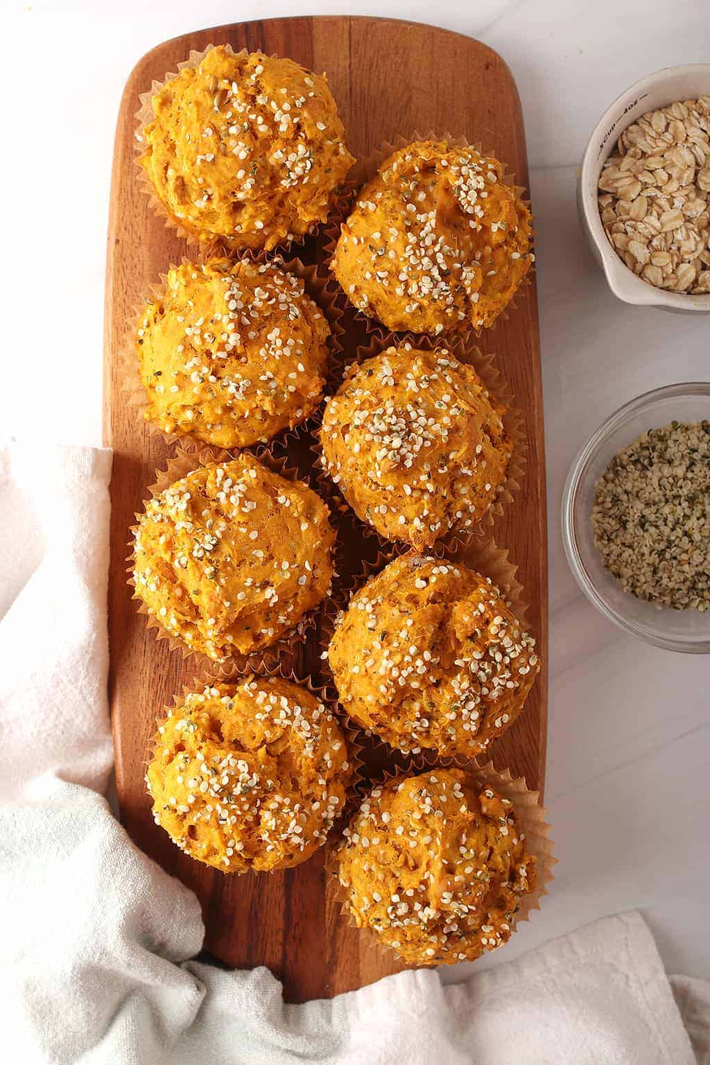 8 healthy pumpkin hemp muffins on a wooden cutting board with two off to the side on a white tabletop