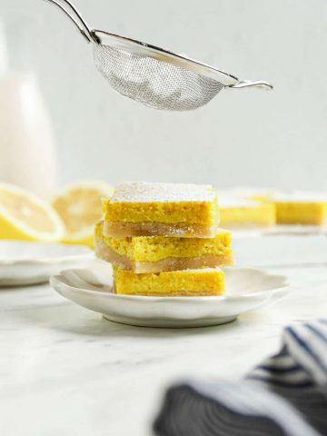 three lemon bars on top of each other with powdered sugar