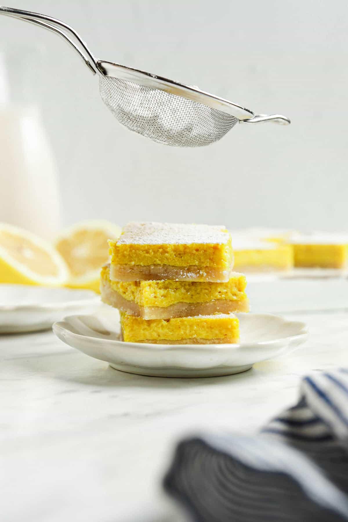 three vegan lemon bars on one white plate