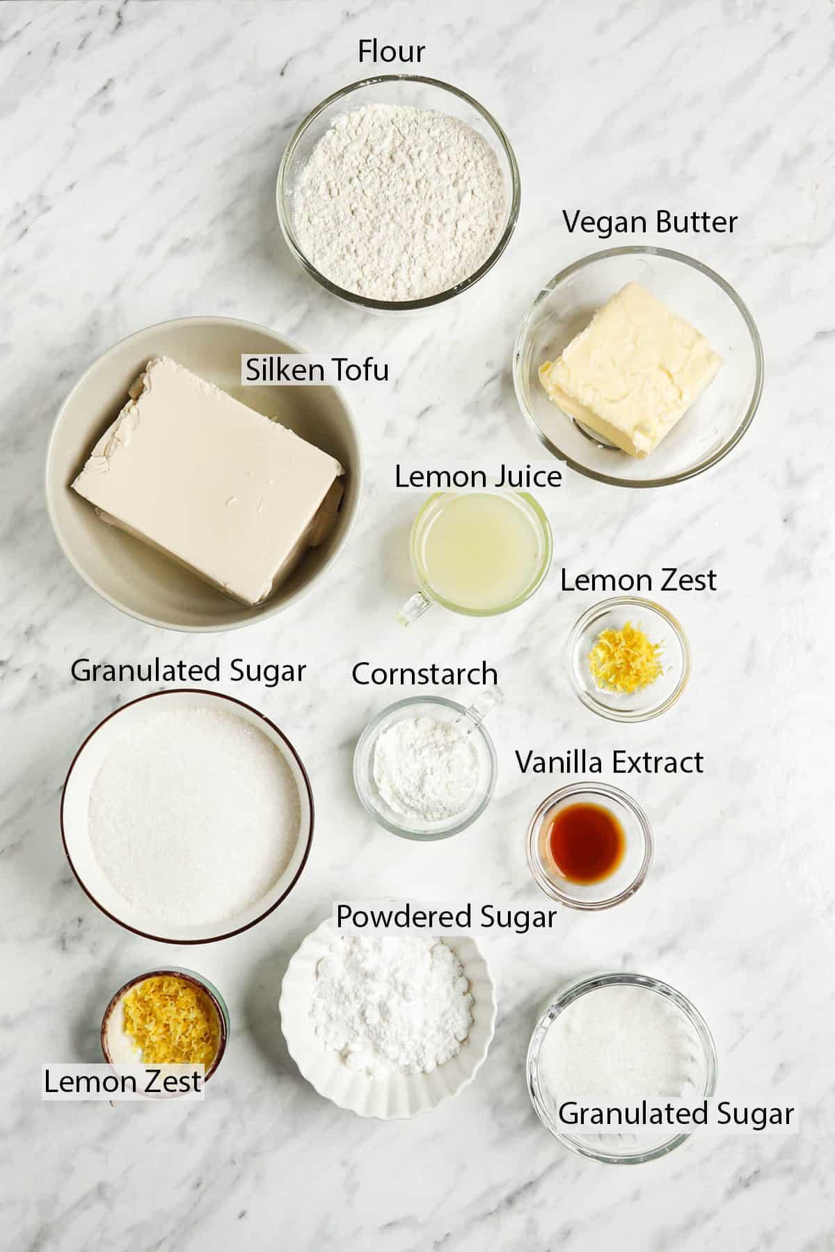 sugar, lemon juice and zest, vanilla, flour, cornstarch, tofu, vegan butter on white surface