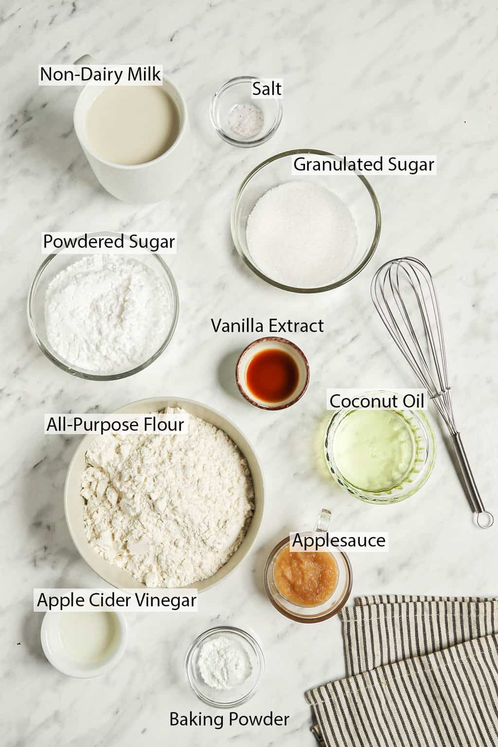 Ingredients for glazed doughnuts measured out and placed on a marble countertop.