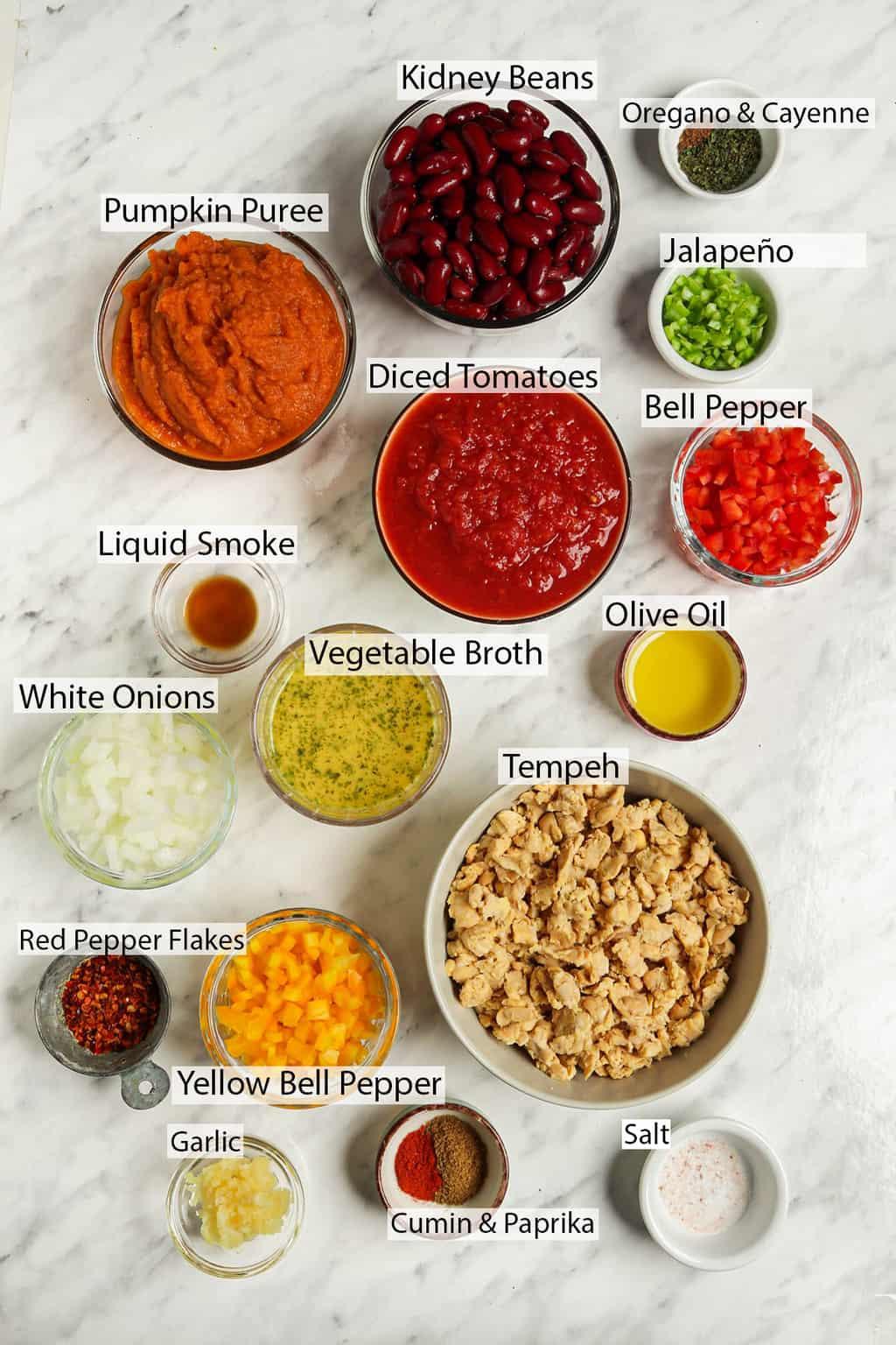 ingredients shot of gluten-free vegan pumpkin chili featuring kidney beans, oregano, cayenne, jalapeño, pumpkin puree, tomatoes, liquid smoke, olive oil, vegetable broth, white onions, tempeh, red pepper flakes, yellow bell pepper, garlic, salt, cumin, paprika,
