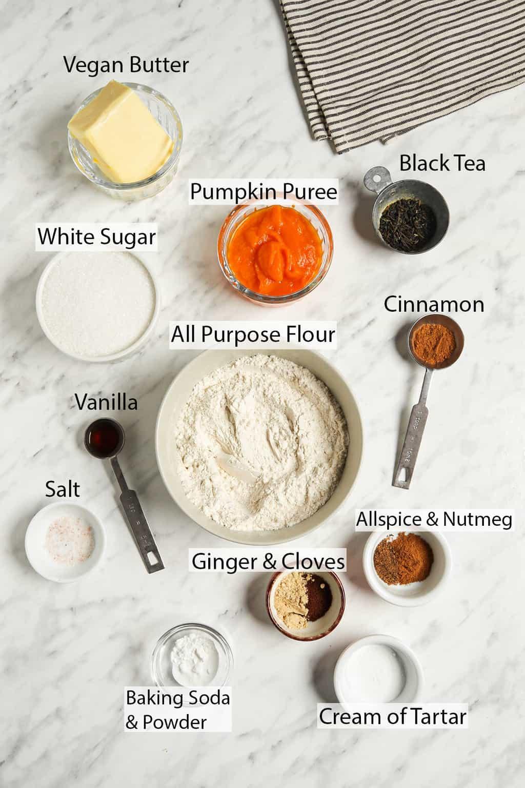 ingredients shot with linen including vegan butter, pumpkin puree, black tea, granulated sugar, all-purpose flour, cinnamon, vanilla, salt, ginger, cloves, allspice, nutmeg, baking soda and powder, and cream of tartar