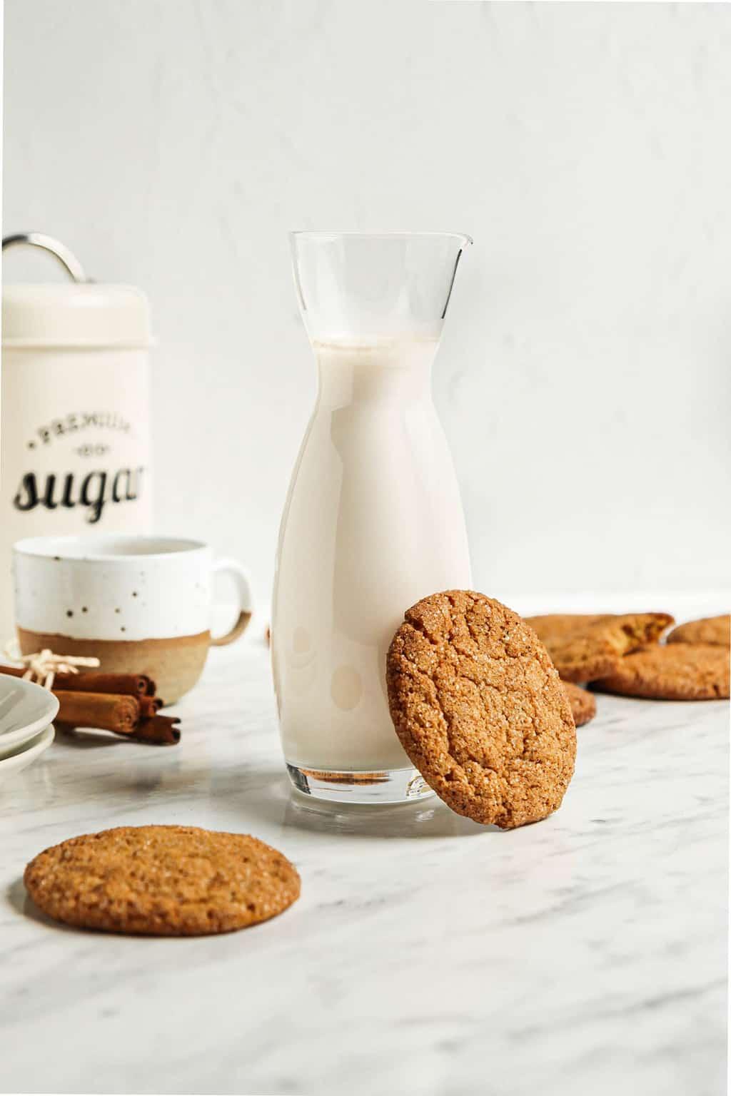 carafe of milk with pumpkin snickerdoodle on the side. pumpkin snickerdoodles in the background with mug, cinnamon, and sugar.