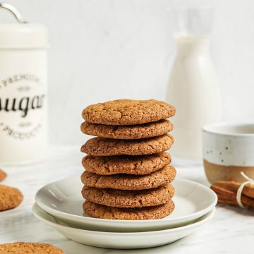 seven cookies in a stack on two white plates with sugar and milk in background