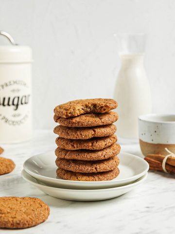 stack of seven pumpkin snickerdoodle cookies on two white plates with cinnamon and milk in background