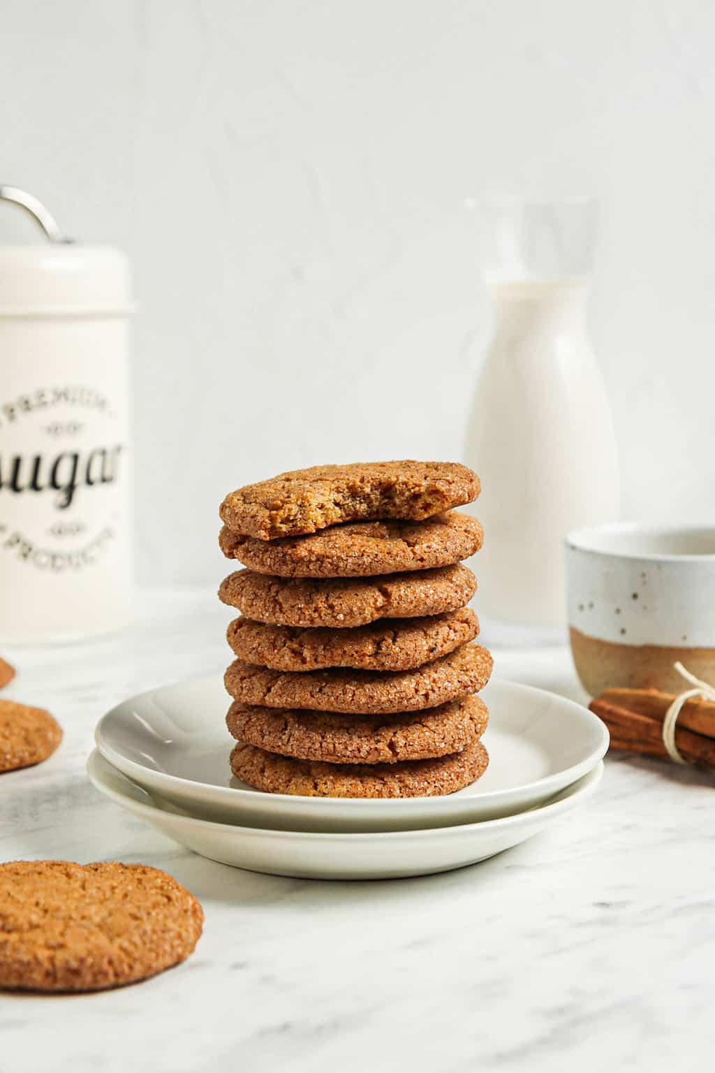 one stack of seven cookies on two white plates with sugar and milk in background