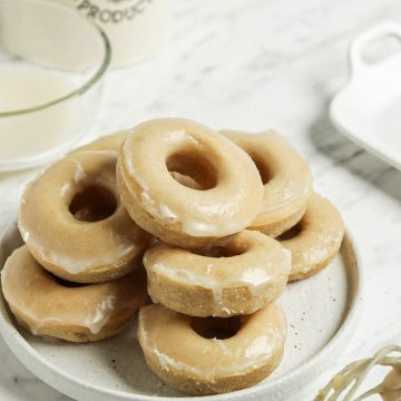 plate of vegan donuts with vanilla glaze and coffee container in background