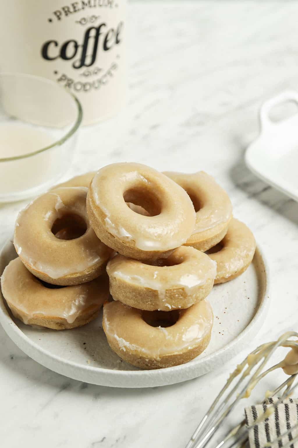 one plate filled with a group of glazed doughnuts from the vegan donut recipe ready to be eaten. One tin of coffee in the background