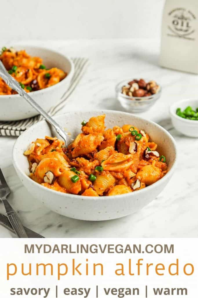 pinterest graphic of pumpkin alfredo in white bowl with utensil and hazelnuts and green onions