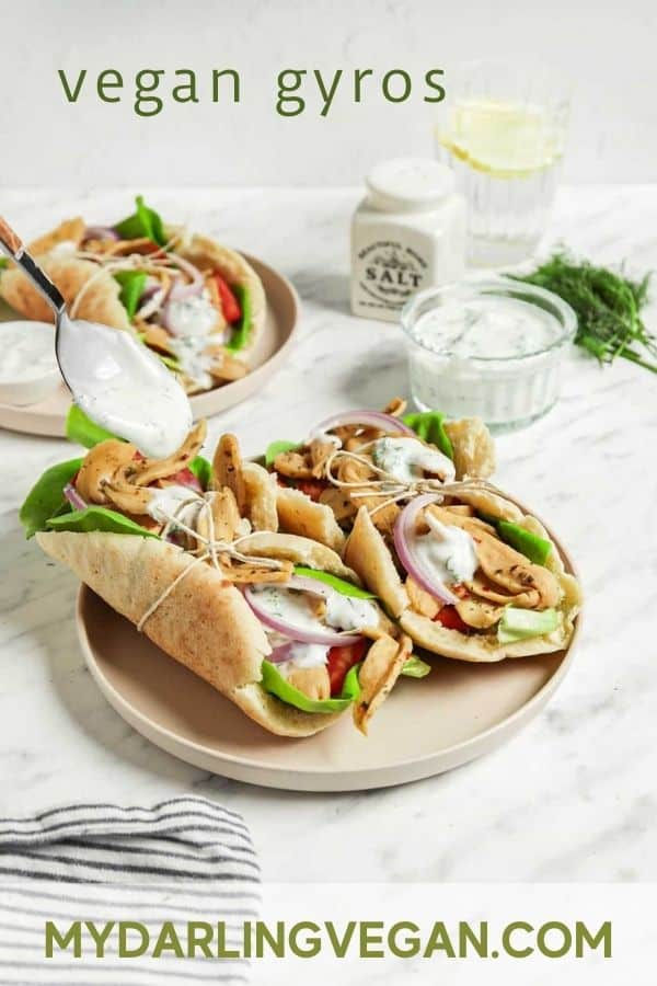 front view of tzatziki sauce being poured over gyro sandwiches on plate