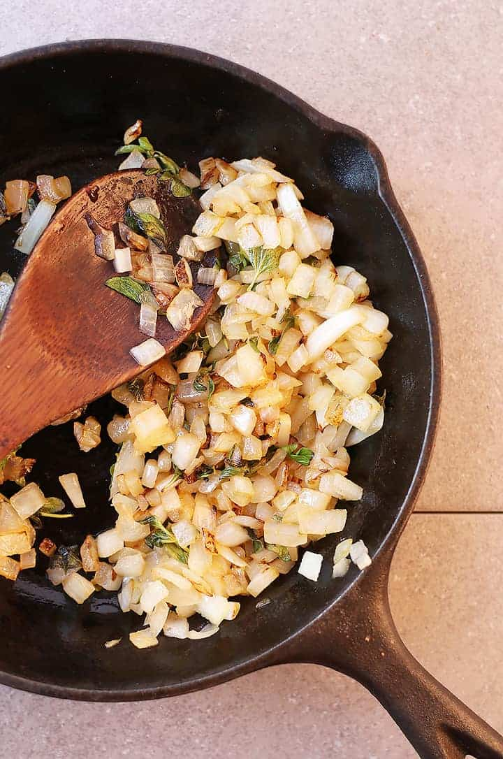 Sautéed onions and herbs in a small cast iron skillet.
