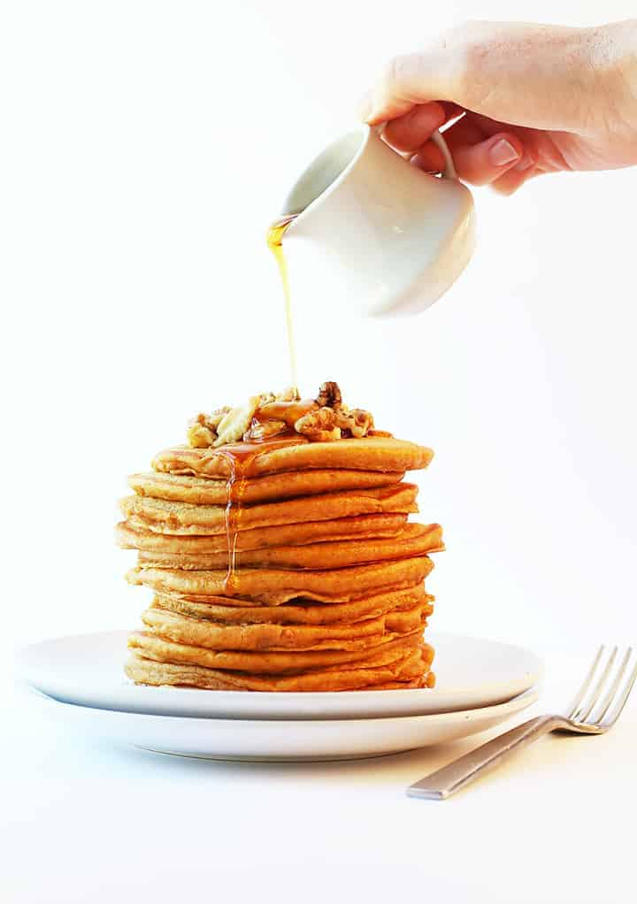 Stack of vegan Pumpkin Pancakes with maple syrup poured from above.