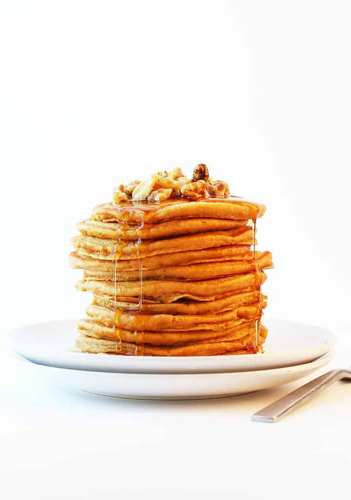Stack of Vegan Pumpkin Pancakes with pecans and maple syrup.