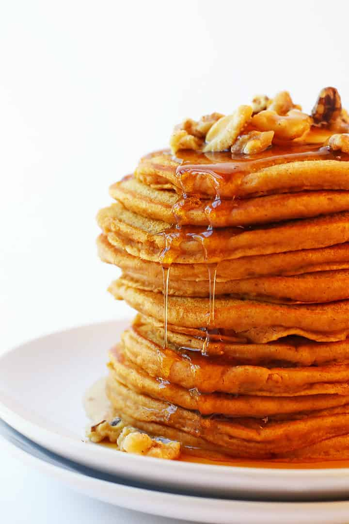 Close up of a stack of vegan Pumpkin Pancakes with syrup dripping down the sides.
