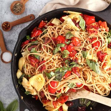 Finished pasta in a cast iron skillet with a wooden spoon