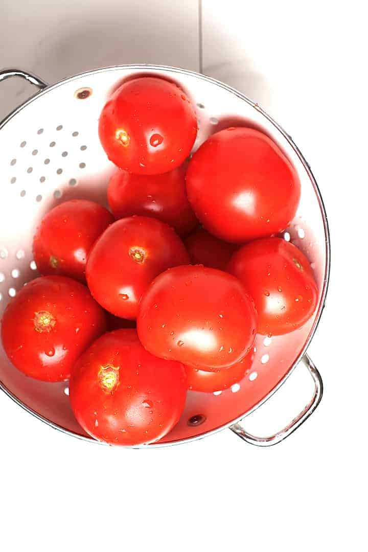 Fresh tomatoes in white colander