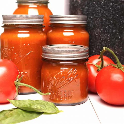 Canned tomato sauce next to canner